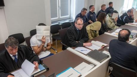 Die vier Angeklagten sitzen neben ihren Anwälten im Verhandlungssaal des Amberger Amtsgerichts. Foto: Armin Weigel