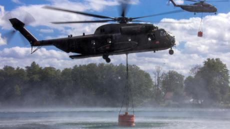 Auftanken: Hubschrauber der Bundeswehr nehmen jeweils 5000 Liter Löschwasser in einem See auf.