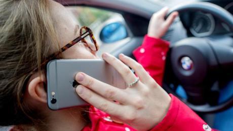 Nur noch schnell einen Anruf entgegennehmen: Viele Autofahrer können selbst am Steuer nicht auf ihr Handy verzichten.