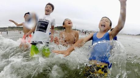 Kinder spielen im Wasser: Nach der Nuklearkatastrophe von Fukushima wurde der Strand zum ersten Mal wieder für Besucher zugelassen.
