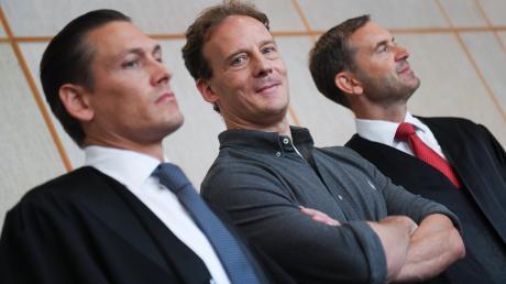 Da ist sein Blick noch selbstbewusst: Der Angeklagte Alexander Falk (Mitte) wartet zusammen mit seinen Verteidigern Daniel Wölky (links) und Björn Gercke im Gerichtssaal des Frankfurter Landgerichts auf den Beginn seines Prozesses.