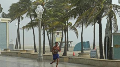Ein Mann rennt am Hollywood Beach durch den Regen. Foto: David Santiago/Miami Herald/AP
