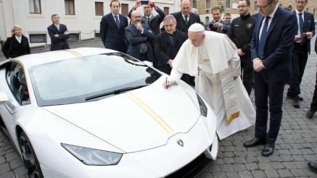 Papst Franziskus signiert den weißen Lamborghini, der ihm vom italienischen Sportwagenhersteller geschenkt wurde. Foto: L'Osservatore Romano/AP