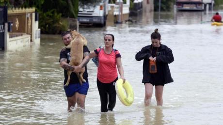 EinHund muss nach heftigen Regenfällen über eine überflutete Straße durch den Ort El Raal im Murcia getragen werden. Foto: Alfonso Duran/AP