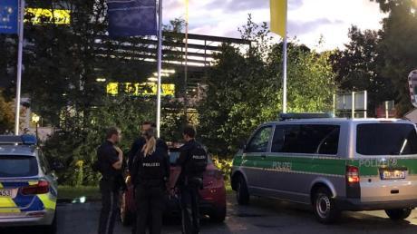 Fahrzeuge von Polizei und Feuerwehr stehen auf dem Parkplatz des Supermarktes in Abensberg. Ein 39 Jahre alter Mann ist aus ungeklärter Ursache erschossen worden. Foto: Alexander Auer/dpa