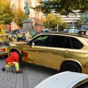 Der goldfarbene SUV wird nahe der Düsseldorfer Königsallee abgeschleppt. Foto: Gerhard Berger