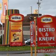 Firmenschilder kennzeichnen die Einfahrt zum Werksgelände des nordhessischen Wurstherstellers Wilke. Foto: Uwe Zucchi/dpa