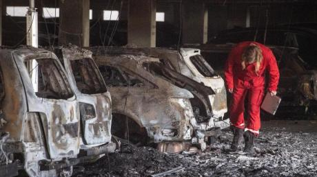 Ein Sachverständiger inspiziert in dem Parkhaus am völlig ausgebrannte Autos. Foto: Bernd Thissen/dpa
