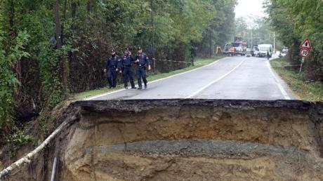 Carabinieri begutachten eine durch heftige Regenfälle zerstörten Straße.