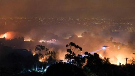 Ein Hubschrauber fliegt über einem Wohngebiet, das vom sogenannten «Getty»-Feuer betroffen ist. Foto: David Crane/Orange County Register via ZUMA/dpa