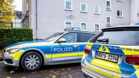 Polizeifahrzeuge vor dem Mehrfamilienhaus in Detmold, in dem eine 15-Jährige ihren dreijährigen Halbbruder erstochen haben soll. Foto: Guido Kirchner/dpa