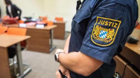 Ein Justizbeamter zu Beginn eines Prozesses im Sitzungssaal vom Landgericht München II.