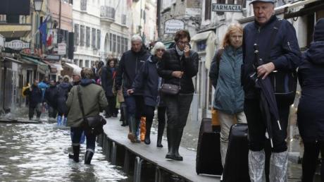Touristen ziehen ihr Gepäck über provisorische Gehsteige. Foto: Luca Bruno/AP/dpa
