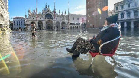Eine Frau sitzt auf einem Stuhl im Hochwasser auf dem Markusplatz. Foto: Claudio Furlan/LaPresse via ZUMA Press/dpa
