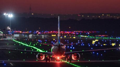 Ein Passagierflugzeug rollt im letzten Licht der untergehenden Sonne über die Rollbahn des Frankfurter Flughafens.
