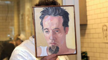 Sebastian Brecht, der sich nie fotografieren lässt, hält sich ein Portrait vor sein Gesicht, das die Künstlerin Alix Bailey von ihm gemalt hat.