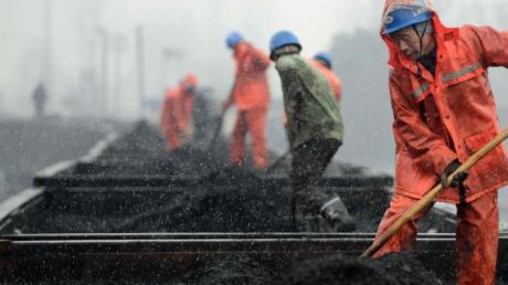 Das Archivbild zeigt Arbeiter auf einem mit Kohle beladenen Zug. China fördert weiter Kohle für seinen Energiebedarf - die Gruben gelten jedoch als sehr anfällig für Unglücke. Foto: Hu Guolin/epa/dpa
