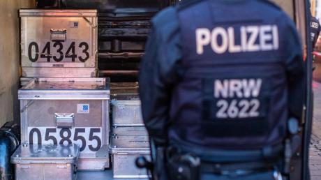 Polizeibeamte sichern kistenweise Beweise nach einer Durchsuchung in einem Geschäft.