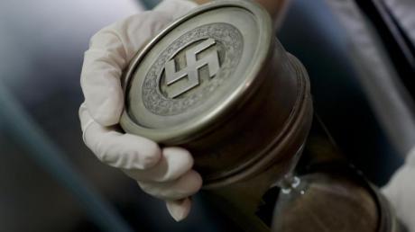 Ein Mitglied der Bundespolizei hält am 16.06.2017 im Interpol-Hauptquartier in Buenos Aires (Argentinien) eine Sanduhr mit Hakenkreuz. Das Auktionshaus Hermann Historica versteigert ähnliche Nazi-Devotionalien.