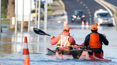 Zwei Männer paddeln mit ihren Kajaks durch die überflutete Straße in Palavas-les-Flots nach einem nächtlichen Sturm in Südfrankreich.