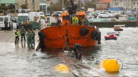 Ein Schlepper der Guardia Civil zieht ein gut 20 Meter langes Drogen-U-Boot aus dem Wasser, das vor der Küste der Region Galicien abgefangen worden war.