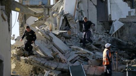 Nach einem Erdbeben durchsuchen Rettungskräfte ein zerstörtes Gebäude.