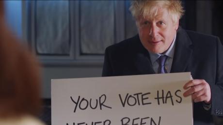 """Boris Johnson, Premierminister von Großbritannien, hält in einem Wahlwerbespot der Konservativen ein Schild mit der Aufschrift """"Your vote has never been more important""""."""