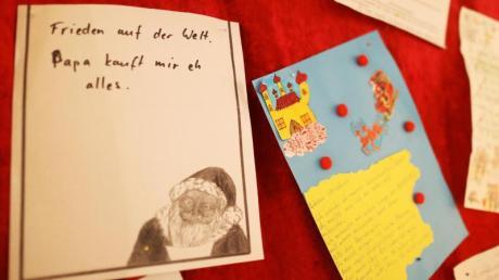 """Ein Wunschzettel mit dem Satz """"Frieden auf der Welt - Papa kauft mir eh alles"""" hängt in der Christkind-Postfiliale an der Wand."""