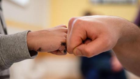 Ein Insasse gibt in der Vater-Kind-Gruppe in der JVA Nürnberg seinem Sohn einen Fist Bump.