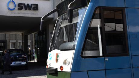 Vor der Zentrale der Augsburger Stadtwerke steht eine Straßenbahn.