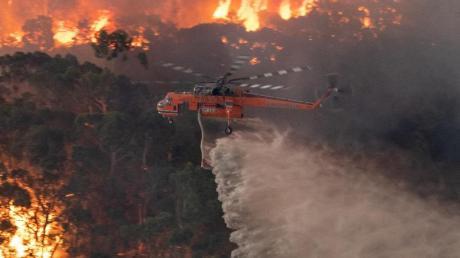 Ein Löschhubschrauber fliegt über ein Buschfeuer in der Nähe von Bairnsdale in der Region East Gippsland Shire im Bundesstaat Victoria.