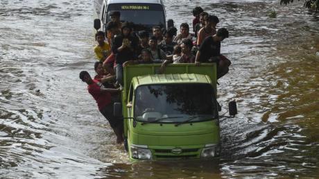 Menschen stehen auf der Ladefläche eines Transporters, um eine überflutete Straße in Jakarta zu passieren.