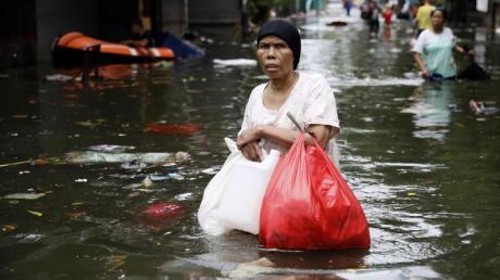 Eine Frau geht durch das Hochwasser einer überfluteten Straße in Jakarta.