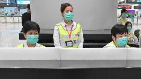 Vorsorge in Hongkong: Mitarbeiter des Gesundheitswesens untersuchen am Bahnhof West Kowloon Station Reisende auf ihren Gesundheitszustand.