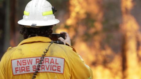Ein Feuerwehrmann fotografiert mit seinem Smartphone eines der Buschfeuer bei Tomerong. Rund 2.300 Feuerwehrleute sind im Bundesstaat New South Wales bei etwa 110 Buschbrände im Einsatz.