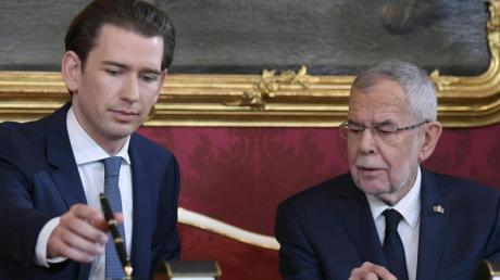Sebastian Kurz, Bundeskanzler von Österreich, unterzeichnet seine Ernennungsurkunde neben Bundespräsident Alexander Van der Bellen.