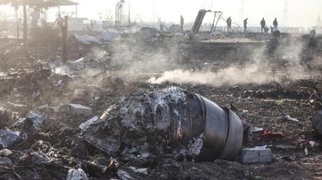 Rauchende Trümmer einer Turbine der ukrainischen Passagiermaschine am Absturzort.