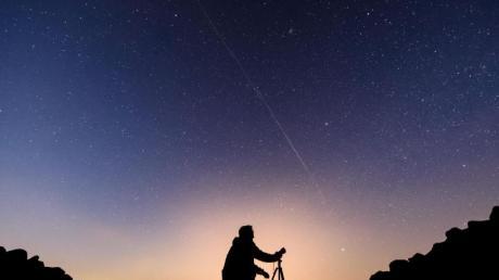Ein Fotograf steht vor einem Nachthimmel, an dem die Bewegung von Starlink-Satelliten als leuchtende Spur (Bildmitte) sichtbar wird.
