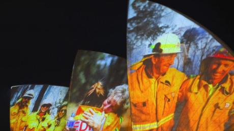 Symbolischer Dank an die Einsatzkräfte in Sydney: Auf die großen Segel des Opernhauses werden als Zeichen der Solidarität Bilder von Feuerwehrleuten projiziert.