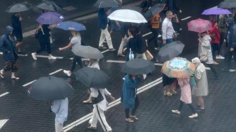 Fußgänger schützen sich mit Regenschirmen vor starkem Regen. Der Niederschlag bringt angesichts der anhaltenden Buschbrände in New South Wales etwas Entlastung für die Einsatzkräfte.