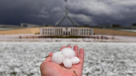 Auf einer Hand liegen Golfballgroße Hagelkörner, die bei einem schweren Hagelsturm vor dem Parlamentsgebäude niedergegangen sind.