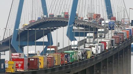 Mit Containern beladene Lastwagen stauen sich auf der Köhlbrandbrücke im Hamburger Hafen.