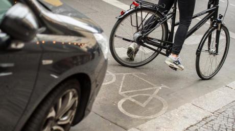 Eine Radfahrerin umfährt ein auf einem Radweg abgestelltes Auto.