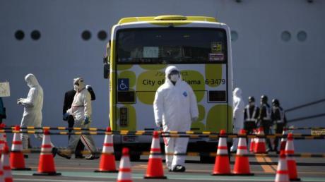 Ein Bus wird inspiziert, bevor die ersten Passagiere des unter Quarantäne stehenden Kreuzfahrtschiffs «Diamond Princess» einsteigen.
