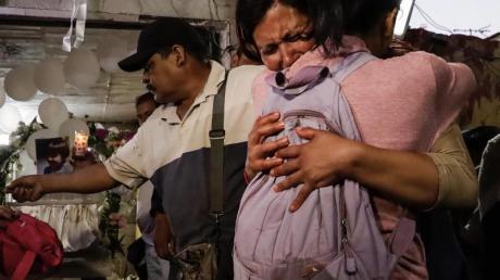 Zwei Frauen umarmen sich und weinen auf der Totenwache eines ermordeten siebenjährigen Mädchens.