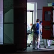 Mitarbeiter aus dem Leber- und Infektionszentrum des Universitätsklinikums in Düsseldorf nehmen den ersten mit dem Coronavirus Infizierten in NRW in Empfang.