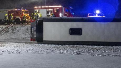 Ein Reisebus liegt umgestürzt neben der B10 bei Tomerdingen nördlich von Ulm in einem Feld. Bei schneeglatter Fahrbahn und starkem Wind kam der Bus von der Straße ab.