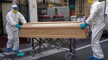 Medizinisches Personal trägt einen Sarg mit dem Leichnam einer 87-jährigen Frau aus einem Hotel im italienischen Laigueglia.