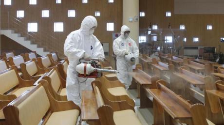 Zwei Arbeiter in Schutzkleidung versprühen Desinfektionsmittel in einer Kirche in Südkorea.