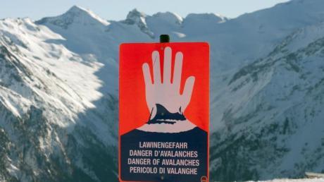 Ein Schild warnt neben einer Skipiste vor Lawinengefahr.